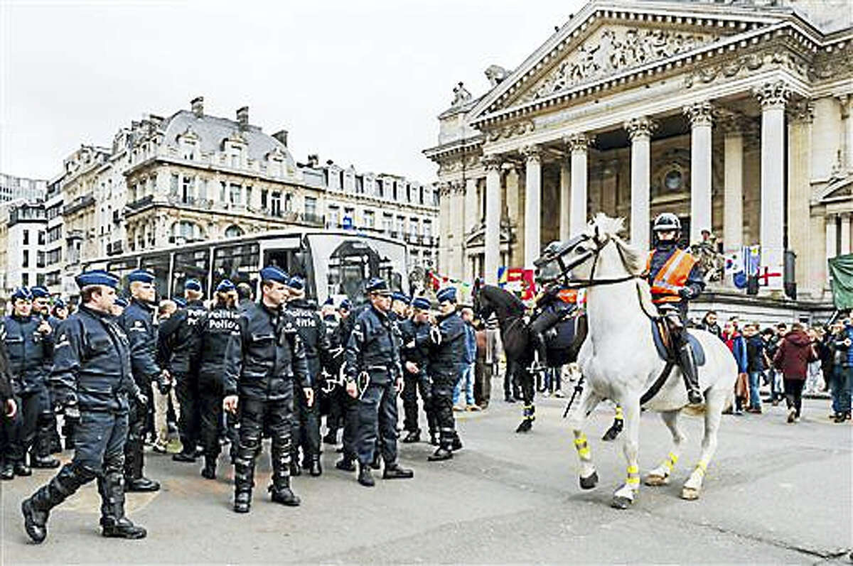 Police secure a zone around a police bus for detained people, at the Place de la Bourse in Brussels, Belgium, Saturday, April 2, 2016. Authorities had banned all marches in Brussels, after a far-right group announced its plans to hold an anti-Muslim rally in the city.