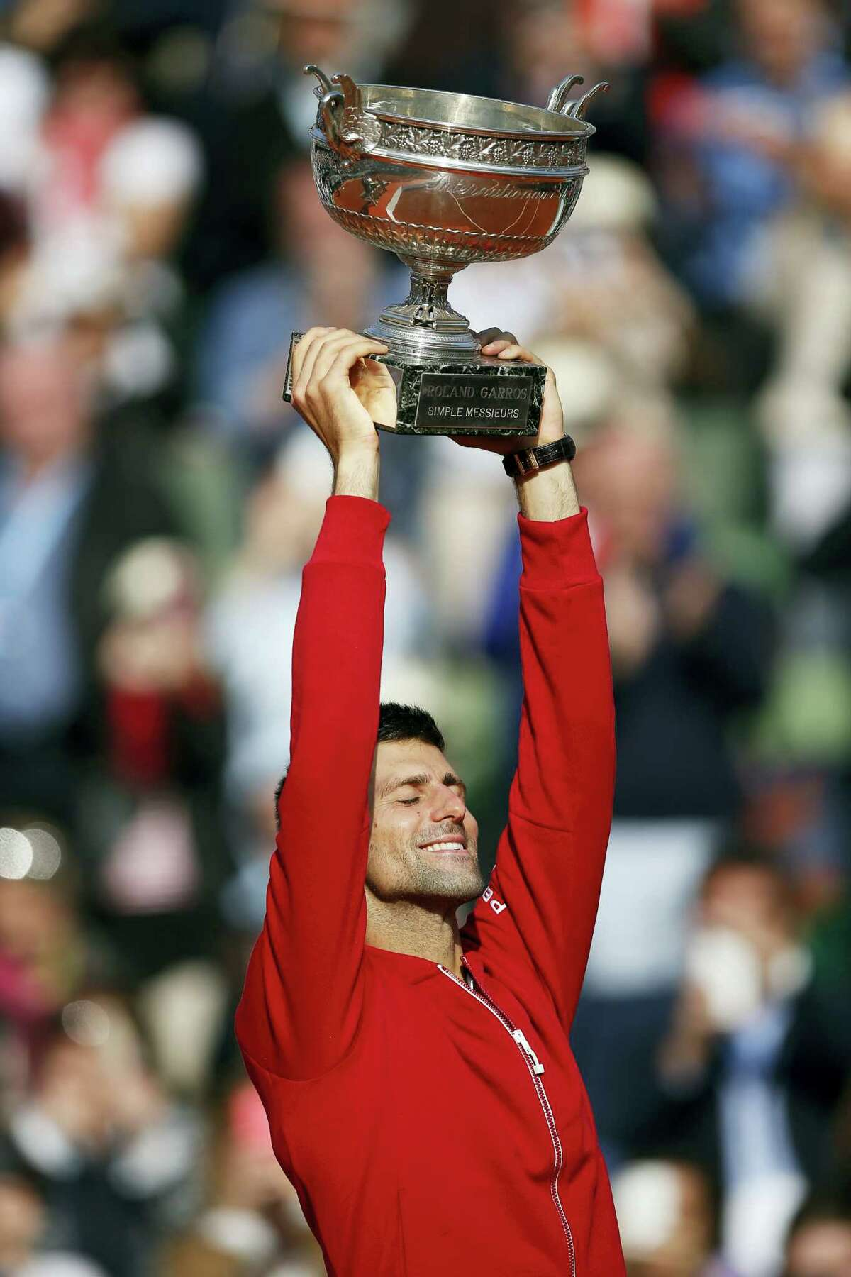 Serbia's Novak Djokovic gives a thumbs up as he holds the trophy after winning the final of the French Open tennis tournament against Britain's Andy Murray in four sets 3-6, 6-1, 6-2, 6-4, at the Roland Garros stadium in Paris, France, Sunday, June 5, 2016.