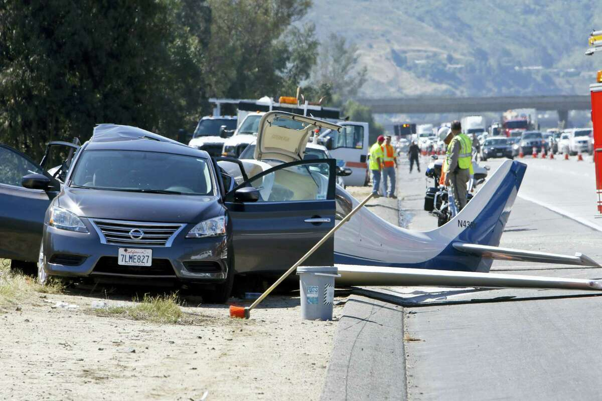 Emergency personnel investigate the scene of plane crash, Saturday, April 2, 2016 in Fallbrook, Calif. A small plane crashed on a Southern California freeway Saturday and struck a car, killing one person and injuring five others, authorities said.