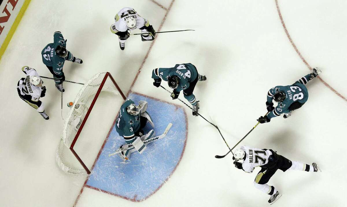 Pittsburgh Penguins and San Jose Sharks players battle for position next to the goal during overtime in Game 3 of the Stanley Cup Finals on Saturday.