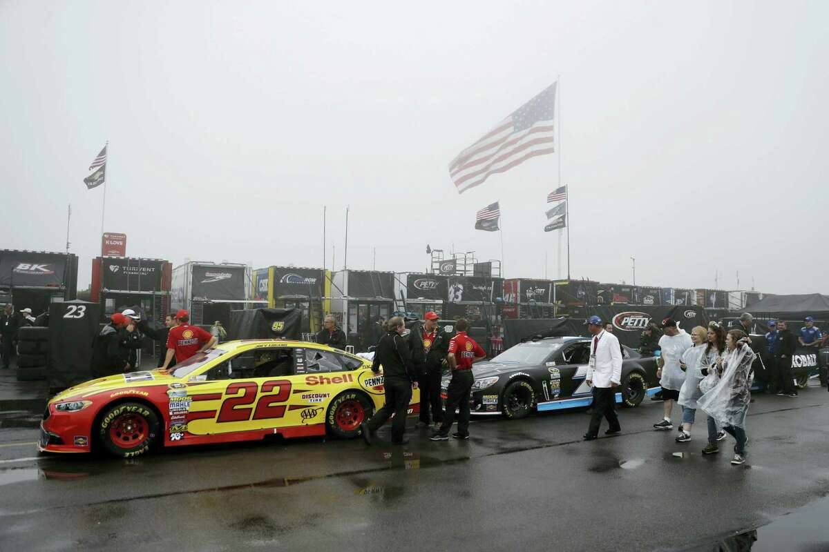 Crew members wait with their cars for an inspection before Sunday's race in Long Pond, Pa. The race was postponed due to rain.