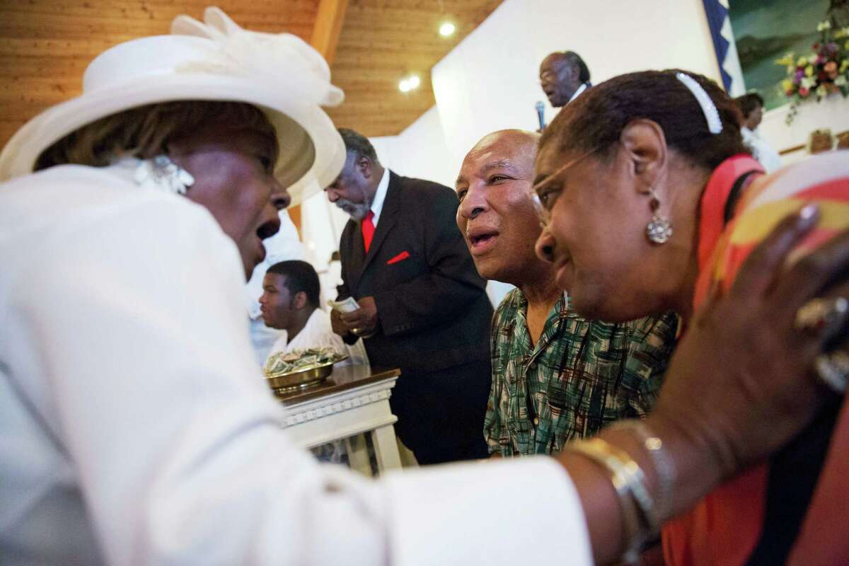 Rahaman Ali, center, brother of Muhammad Ali, and his wife Caroline Ali, right, are greeted by Margaret Machomes as parishioners line up to make a donation in support of the couple during a service at King Solomon Missionary Baptist Church where Ali's father worshipped and where Muhammad Ali would occasionally accompany him, Sunday, Louisville, Ky.