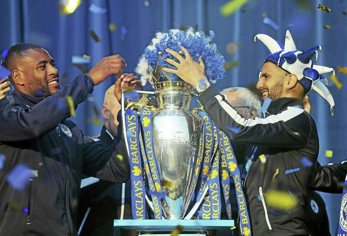 Leicester City captain Wes Morgan, left, and Leicester's Riyad Mahrez place a Leicester wig in club colours on the Premier League Trophy during a victory parade.
