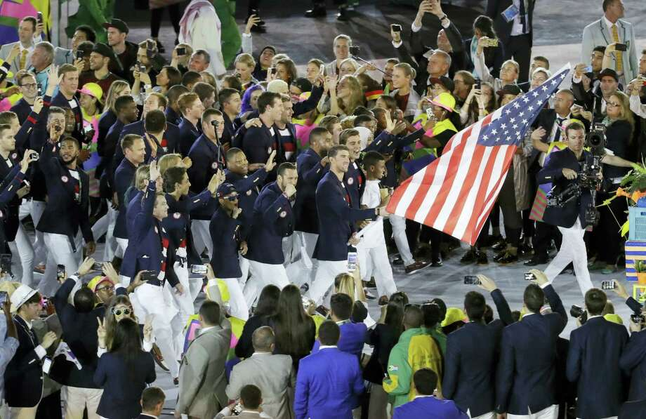 Michael Phelps carries the flag of the United States during the opening ceremony for the 2016 Summer Olympics in Rio de Janeiro, Brazil, on Friday. Photo: Markus Schreiber — The Associated Press  / Copyright 2016 The Associated Press. All rights reserved. This material may not be published, broadcast, rewritten or redistribu