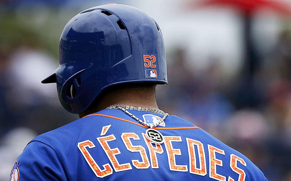 Yoenis Cespedes's No. 52 necklace is turned around on his back as he walks off the field during a recent spring training game in Port St. Lucie, Fla.