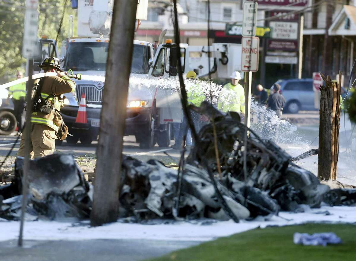 Firefighters use foam to extinguish the fire of a demolished aircraft after the plane crashed on Main Street in East Hartford on Tuesday. Authorities said at least one person is dead and another is injured after a small airplane crashed near the Connecticut River. Jim Michaud — Journal Inquirer via AP)