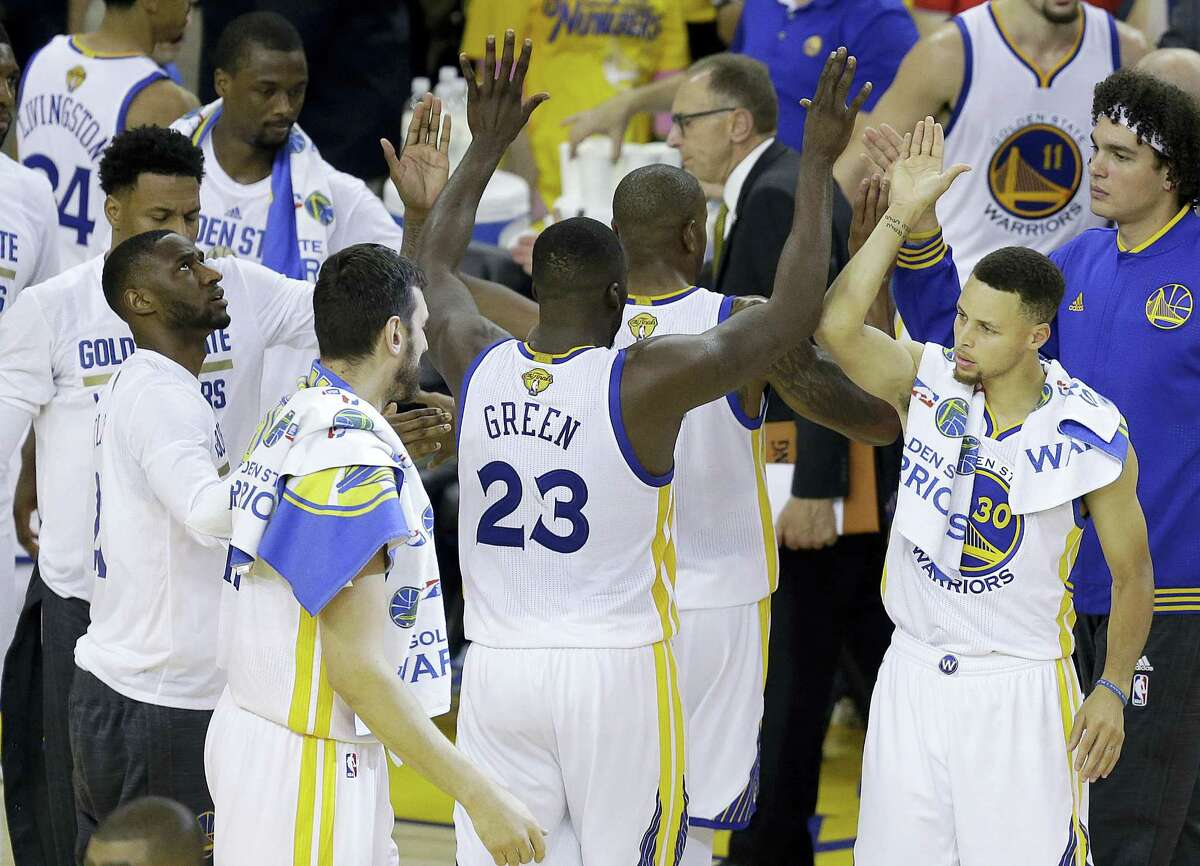 Warriors guard Stephen Curry, right, forward Draymond Green (23) and teammates celebrate during the second half of Game 2 of the NBA Finals on Sunday.