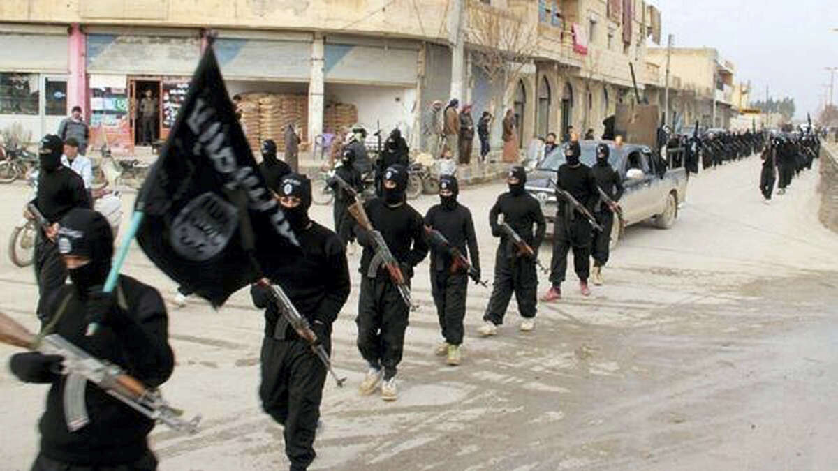 This undated file image posted on a militant website on Jan. 14, 2014, which has been verified and is consistent with other AP reporting, shows fighters from the al-Qaida linked Islamic State of Iraq and the Levant (ISIL), now called the Islamic State group, marching in Raqqa, Syria. The Islamic State group has killed dozens of its own members over the past weeks in a hunt for spies and informants after U.S.-led coalition airstrikes hit a number of high-level jihadis.