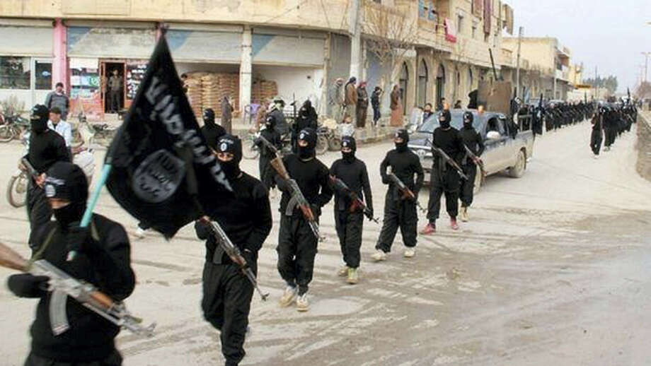 This undated file image posted on a militant website on Jan. 14, 2014, which has been verified and is consistent with other AP reporting, shows fighters from the al-Qaida linked Islamic State of Iraq and the Levant (ISIL), now called the Islamic State group, marching in Raqqa, Syria. The Islamic State group has killed dozens of its own members over the past weeks in a hunt for spies and informants after U.S.-led coalition airstrikes hit a number of high-level jihadis. Photo: Militant Website Via AP, File  / Militant Website