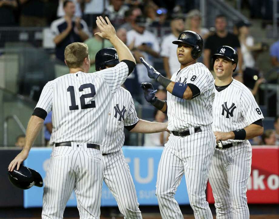 Starlin Castro, second from right, is greeted by teammates Mark Teixeira, right, Chase Headley, left, and Brian McCann after hitting a grand slam during the third inning on Friday. Photo: Seth Wenig — The Associated Press  / Copyright 2016 The Associated Press. All rights reserved. This material may not be published, broadcast, rewritten or redistribu