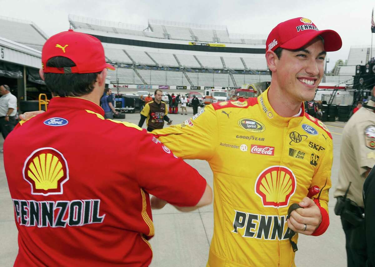 Joey Logano, right, is congratulated by a crew member after wining the pole for Sunday's STP 500 at Martinsville Speedway.