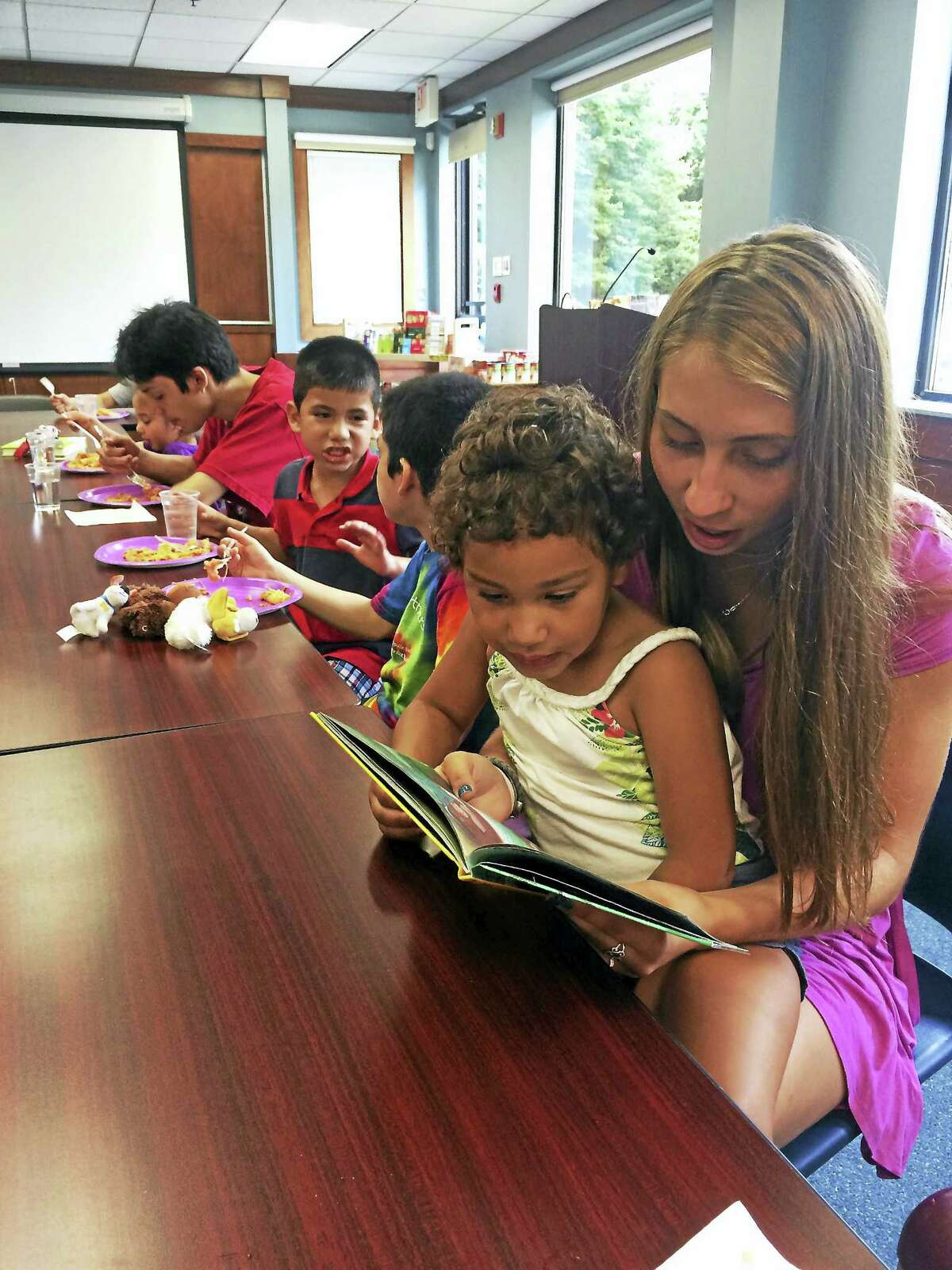 Children enjoy yummy summer lunches and a story at the Kids Cafe in the Clinton Library.