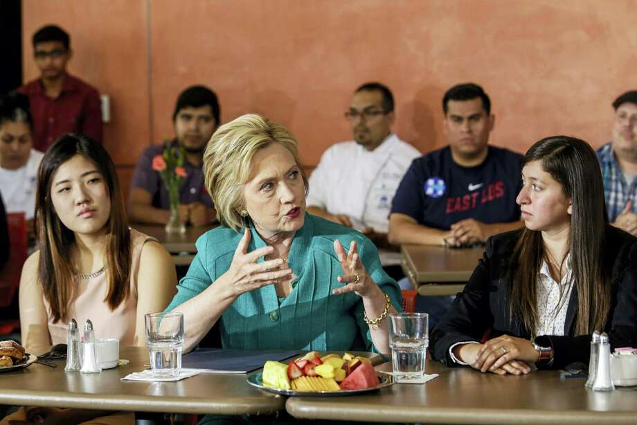 Democratic presidential candidate Hillary Clinton, center, holds a conversation on immigration held at Culinary Arts Institute of Los Angeles Mission College on June 4, 2016 in Sylmar, Calif. Clinton is flanked by Clara Kim, left, and Italia Garcia. They are part of Deferred Action for Childhood Arrivals (DACA) program, an American immigration policy that allows certain illegal immigrants who entered the country before their 16th birthday and before June 2007 to receive a renewable two-year work permit and exemption from deportation. Photo: Irfan Khan/Los Angeles Times Via AP  / Los Angeles Times