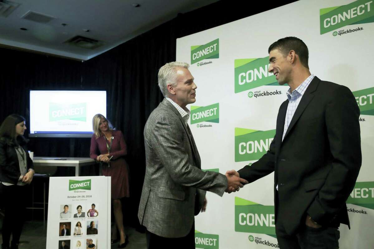 Former Olympic swimmer Michael Phelps, right, shakes hands with Intuit Chairman and CEO Brad Smith in San Jose.