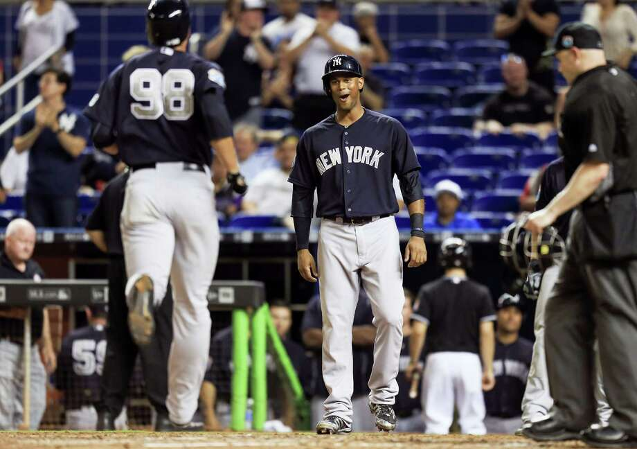 Yankees center fielder Aaron Hicks, center, reacts as right fielder Lane Adams (98) crosses home plate after hitting a two-run home run in the ninth inning on Friday. Photo: Rob Foldy — The Associated Press  / FR171438 AP