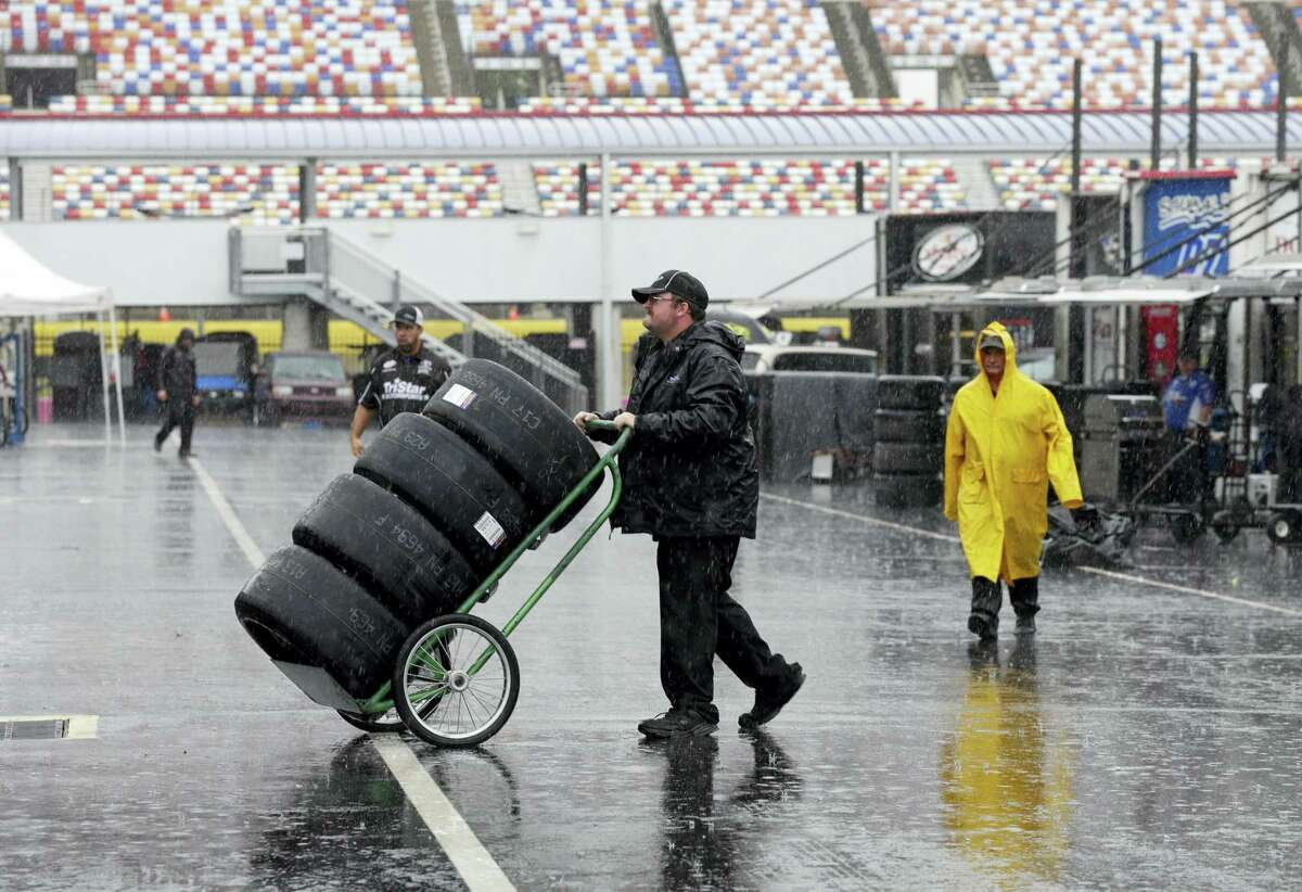 A crew member hauls tires through the NASCAR Xfinity garage in the rain at Charlotte Motor Speedway this past weekend.
