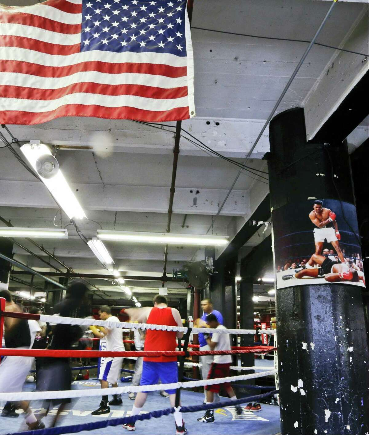 Students take a boxing class at Gleason's Gym next to a photo of Muhammad Ali standing over Sonny Liston Saturday, June 4, 2016, in New York. Ali died Friday at age 74. A memorial service is scheduled for 10 a.m. in Louisville, Kentucky, Ali's hometown. (AP Photo/Frank Franklin II)