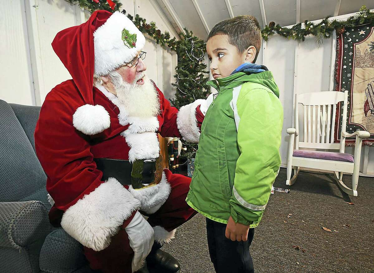 Santa asks Yariel Velazquez, 5, of New Haven what he has on his Christmas list at Thursday's holiday kick-off event on the Green.