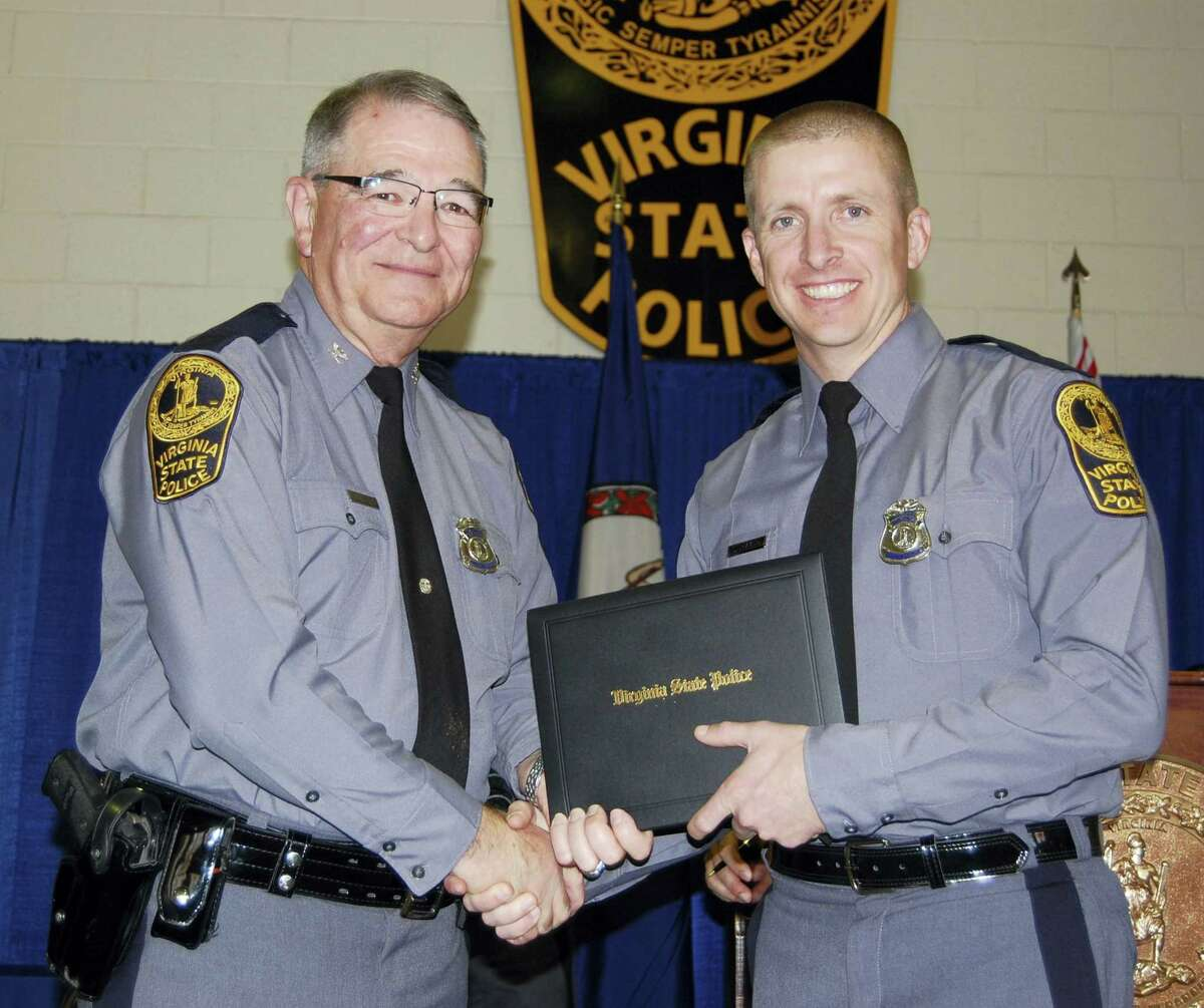 In this November 2014 photo provided by the Virginia State Police, trooper Chad P. Dermyer poses for a photo as he receives his graduation diploma from Superintendent Col. W. Steven Flaherty. Virginia State Police Superintendent Col. Steven Flaherty says Dermyer, died Thursday, March 31, 2016 after being shot multiple times responding to a call at a Greyhound bus station in Richmond. The gunman was shot dead by two other troopers.