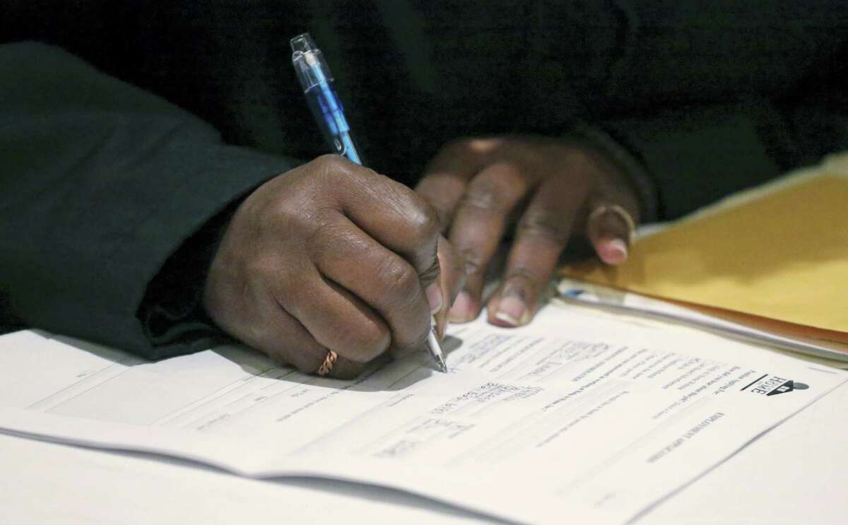 In this April 22, 2015, file photo, a job seeker fills out an application during a National Career Fairs job fair in Chicago. On Thursday, Dec. 1, 2016, the Labor Department reports on the number of people who applied for unemployment benefits the week before.