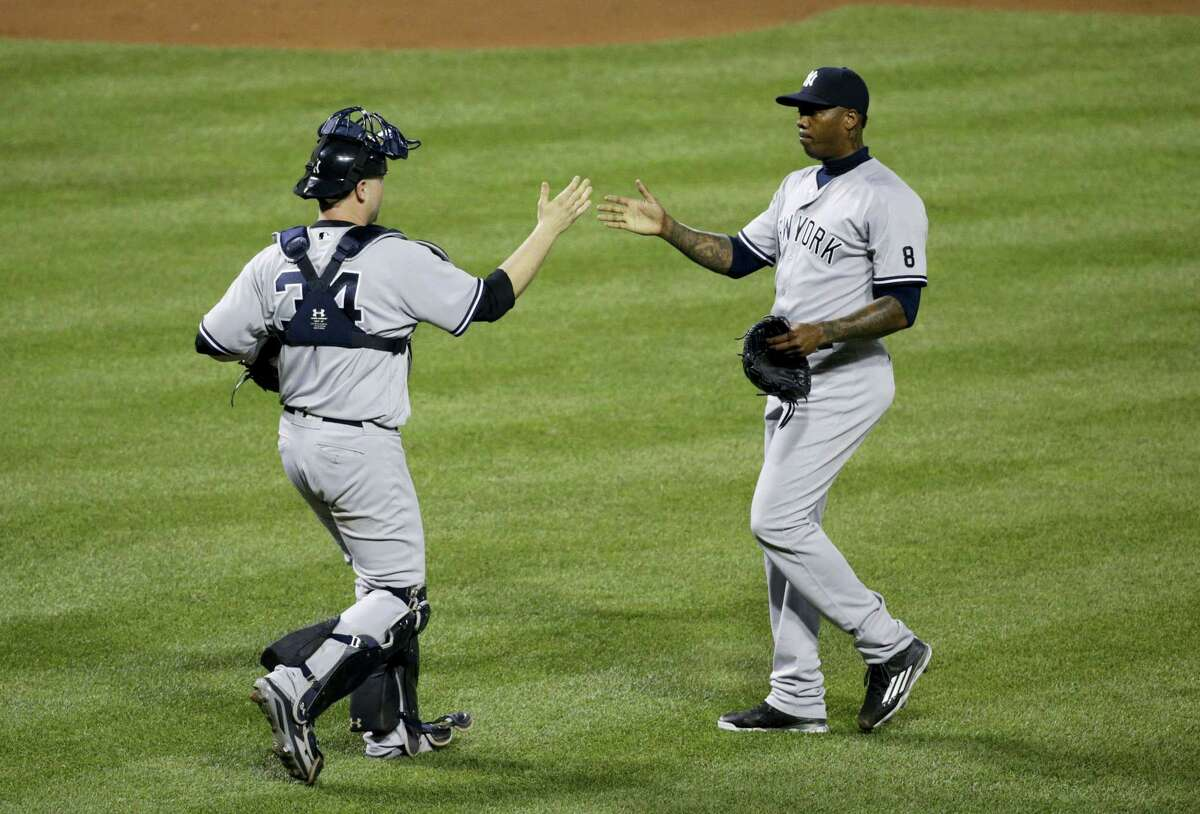 Yankees catcher Brian McCann, left, and relief pitcher Aroldis Chapman high-five after closing out Saturday's win.