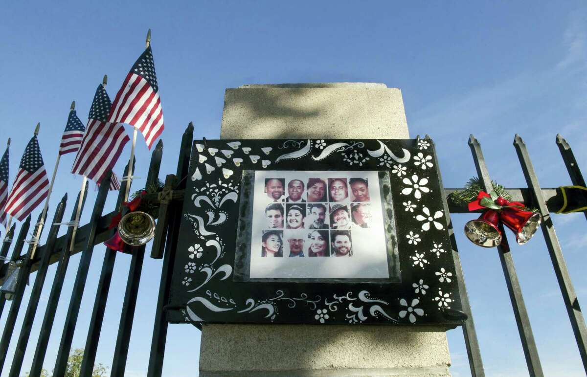 A photo collage showing images of the 14 victims who were killed in the Dec. 2, 2015, San Bernardino terror attack is hung at a makeshift memorial near the Inland Regional Center in San Bernardino, Calif., Thursday, Dec. 1, 2016, where the shooting took place. Friday will mark the one year anniversary of the attack.