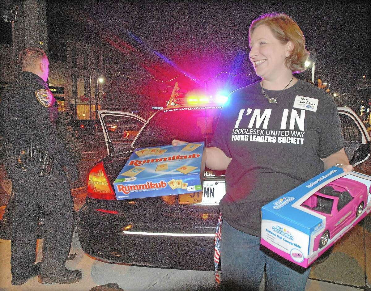 A member of the steering commitee for the Middlesex United Way's Young Leader Society removes toys from the back seat of a Middletown police cruiser during the 2012 Stuff-A-Cruiser toy drive.
