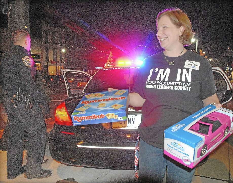 A member of the steering commitee for the Middlesex United Way's Young Leader Society removes toys from the back seat of a Middletown police cruiser during the 2012 Stuff-A-Cruiser toy drive. Photo: File Photo