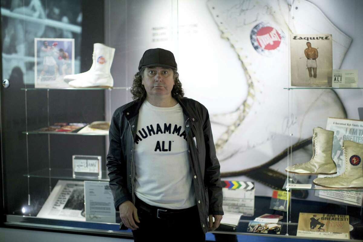 """Advertising Executive Trevor Beattie who worked with Muhammad Ali on advertising and charity campaigns poses for photographs next to items of his Ali memorabilia collection being displayed as part of the """"I Am The Greatest, Muhammad Ali"""" exhibition at the O2 arena, which hosts high profile boxing fights in London, Saturday, June 4, 2016. Ali, the magnificent heavyweight champion whose fast fists and irrepressible personality transcended sports and captivated the world, died according to a statement released Friday by his family. He was 74."""
