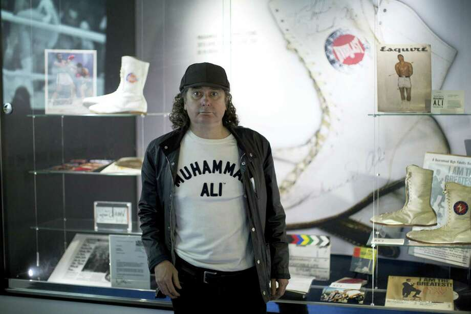"""Advertising Executive Trevor Beattie who worked with Muhammad Ali on advertising and charity campaigns poses for photographs next to items of his Ali memorabilia collection being displayed as part of the """"I Am The Greatest, Muhammad Ali"""" exhibition at the O2 arena, which hosts high profile boxing fights in London, Saturday, June 4, 2016. Ali, the magnificent heavyweight champion whose fast fists and irrepressible personality transcended sports and captivated the world, died according to a statement released Friday by his family. He was 74. Photo: AP Photo/Matt Dunham   / Copyright 2016 The Associated Press. All rights reserved. This material may not be published, broadcast, rewritten or redistribu"""