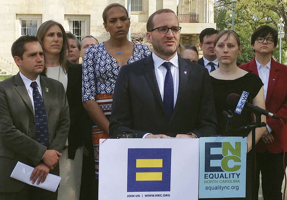 Human Rights Campaign Executive Director Chad Griffin, center, speaks at a news conference at the old state Capitol Building in Raleigh, N.C., on Thursday. Griffin, Equality North Carolina Executive Director Chris Sgro, far left, and others delivered a letter to Gov. Pat McCrory signed by more than 100 corporate executives calling for repeal of a law limiting bathroom options for transgender people and prohibiting local anti-discrimination measures providing protections on the basis of sexual orientation and gender identity. Photo: The Associated Press  / AP