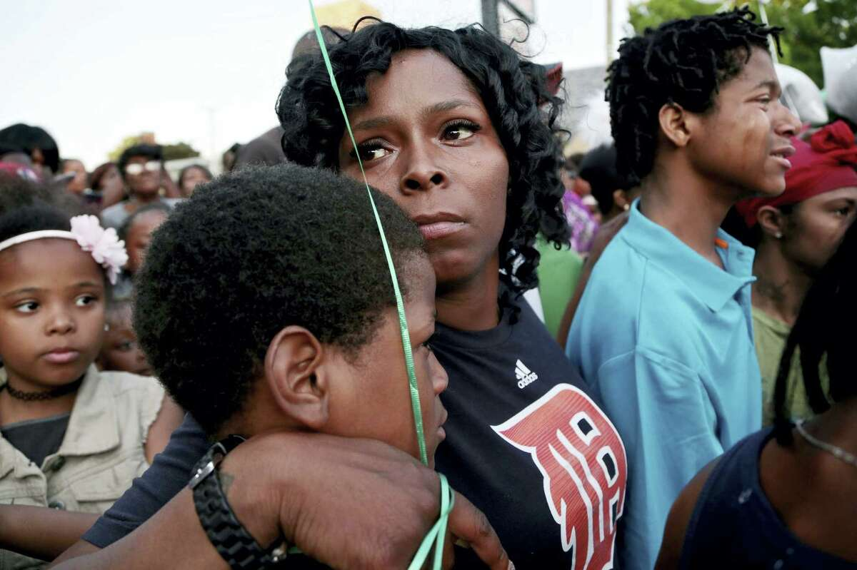 In this Thursday, June 2, 2016 photo, Sierra Adams consoles her son Trayshawn during a vigil at Nino's Market in Detroit, where her cousin Deontae Mitchell, was abducted by a man on Tuesday. A fourth person was arrested Friday in connection with the abduction and death of the teenage Detroit boy, whose body was found this week in a vacant lot, police said.