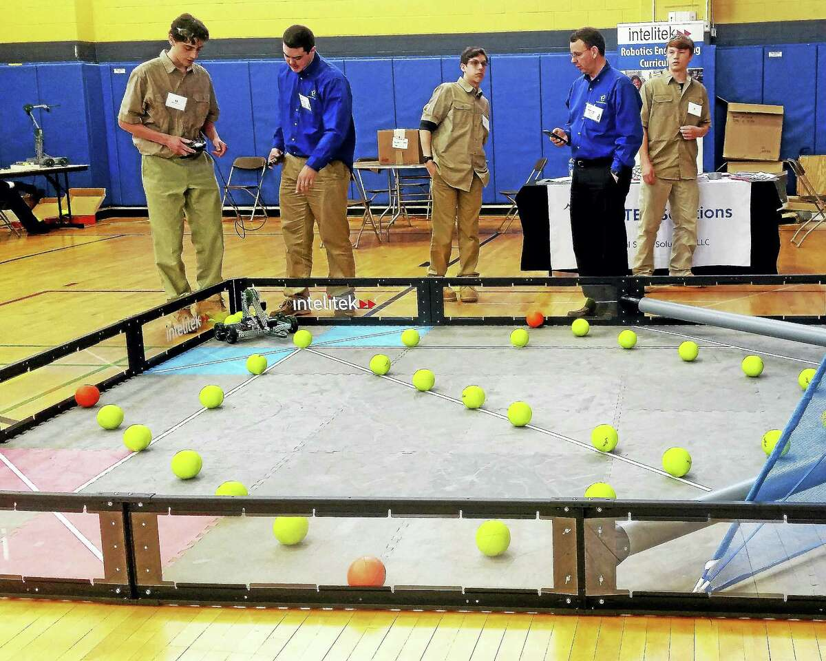 From left, judges stand between Vinal Tech high school juniors Bretton Marks, Talor Matthews and Jason White, as the students prepare to compete in a mobile robotics competition.