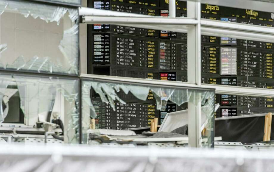 In this March 23, 2016 file photo, an arrivals and departure board is seen behind blown out windows at Zaventem Airport in Brussels. It's unclear when the Brussels Airport will reopen, even after a meeting Friday, April 1 by Prime Minister Charles Michel and key members of the government. Photo: AP Photo — Geert Vanden Wijngaert, Pool / AP Pool