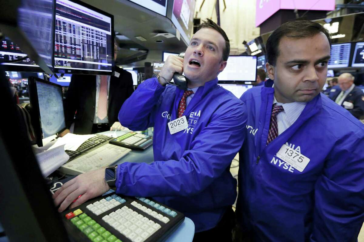 Specialists Frank Masiello, left, and Dilip Patel work on the floor of the New York Stock Exchange Friday.