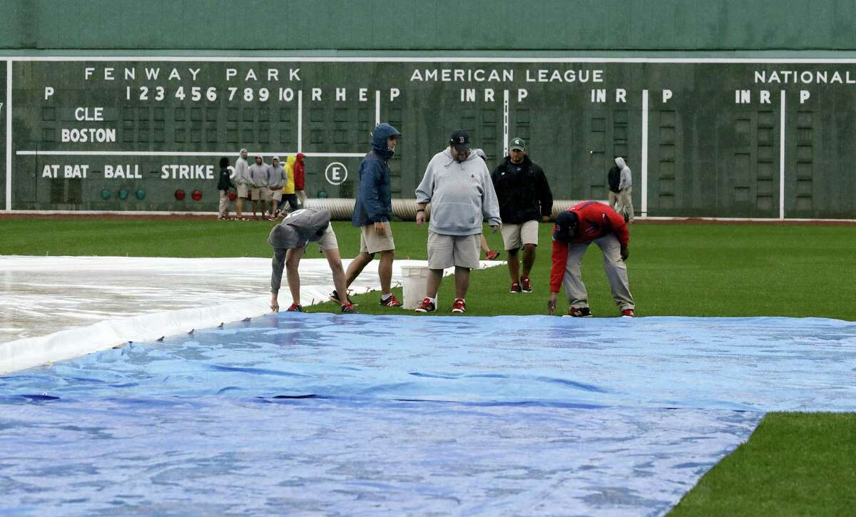 Grounds crew workers secure a tarp at Fenway Park, Sunday in Boston.