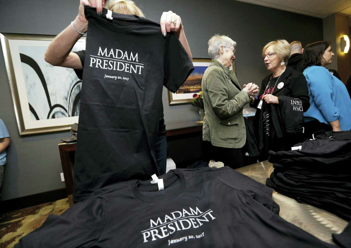 """In this Nov. 8, 2016, file photo, Kathy Schmitt, left, folds T-shirts that she designed, declaring """"Madam President,"""" for sale at an election night party for Democrats in Seattle. Copies of a one-off edition of Newsweek featuring Hillary Clinton that carried the title """"Madam President"""" that were recalled following Clinton's loss in the Nov. 8, 2016, election are being sold for hundreds of dollars on eBay."""