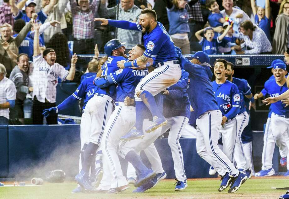 Blue Jays players celebrate their walk-off win over the Rangers on Sunday. Photo: Mark Blinch — The Canadian Press Via AP  / CP