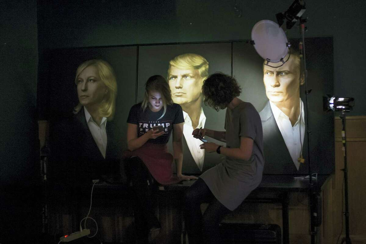 Two women look at their cell phones in front of portraits of U.S. President-elect Donald Trump and Russian President Vladimir Putin, right, as they arrive at the Union Jack pub in Moscow, Russia, to watch a live telecast of the U.S. presidential election on Nov. 9.