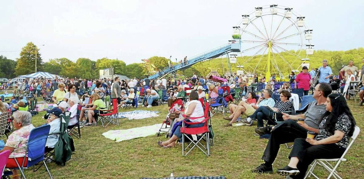 Festival-goers listen to music with the ferris wheel and slide in the background.