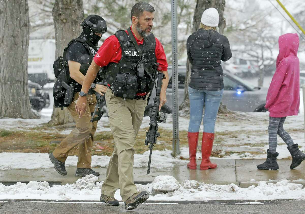 Police officers carry their weapons in front of Mueller Park Junior High after a student fired a gun into the ceiling Thursday, Dec. 1, 2016, in Bountiful, Utah. Police said two fast-acting Utah parents disarmed their teenage son in the hallway of the Utah junior high school Thursday after the teenager brought the family's shotgun and handgun to school, discharging at least one round without injuring anyone.