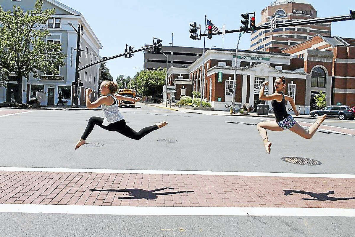 Stage Left Dance students glide above the crosswalk on Main Street in Middletown recently. The studio is celebrating 15 years in the community with a grand reopening celebration Saturday with free demo classes.