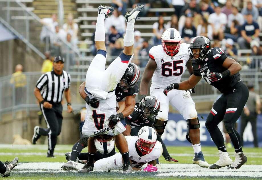 UConn quarterback Bryant Shirreffs is dumped on his head by Cincinnati cornerback James Wiggins during the second half on Saturday. Photo: Winslow Townson — The Associated Press  / FR170221 AP