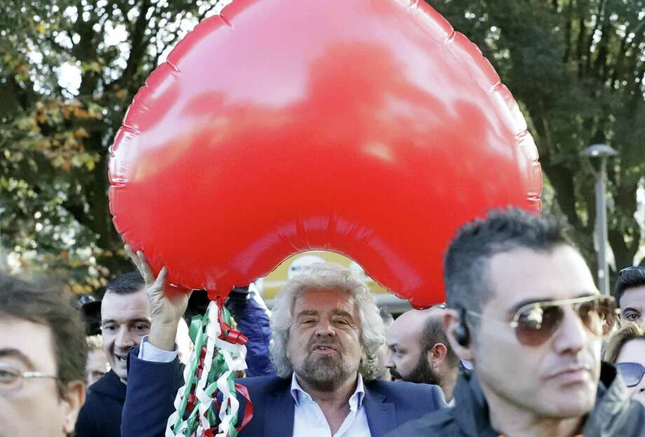 Five Star Movement leader Beppe Grillo holds a heart-shaped balloon adorned with strips in the colors of the Italian flag during a demonstration to support a no vote in Sunday's constitutional referendum in Rome. Photo: AP Photo — Andrew Medichini  / Copyright 2016 The Associated Press. All rights reserved.