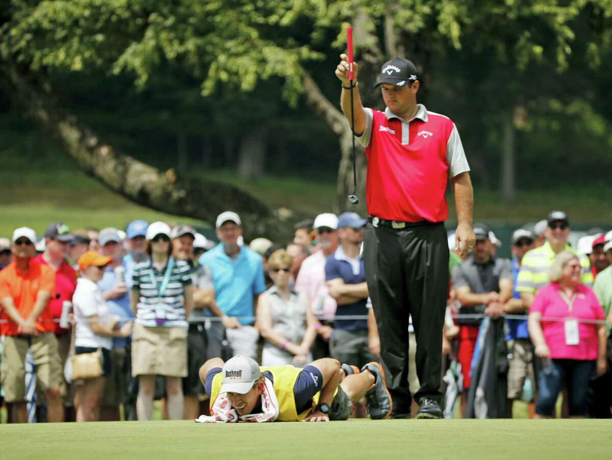 Patrick Reed, top, and his caddie Kessler Karian, bottom line to a putt on the fifth green during the second round of the PGA Championship at Baltusrol last Friday. Reed will play the Travelers this week.