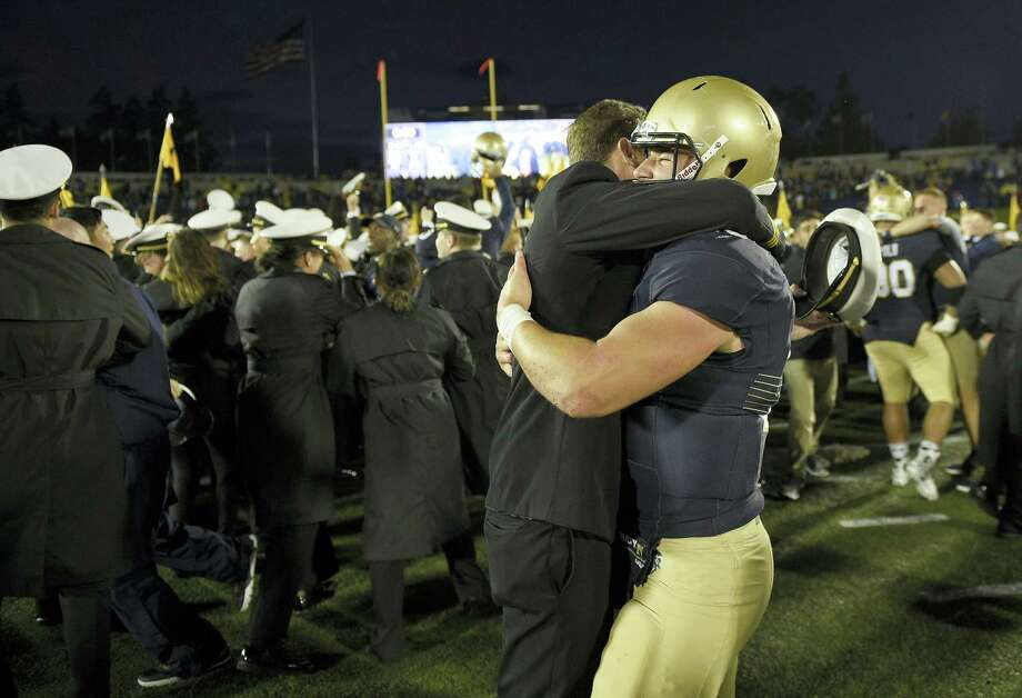 Navy quarterback Will Worth, right, gets a hug from a midshipmen after Saturday's win over Houston. Photo: Nick Wass — The Associated Press  / FR67404 AP