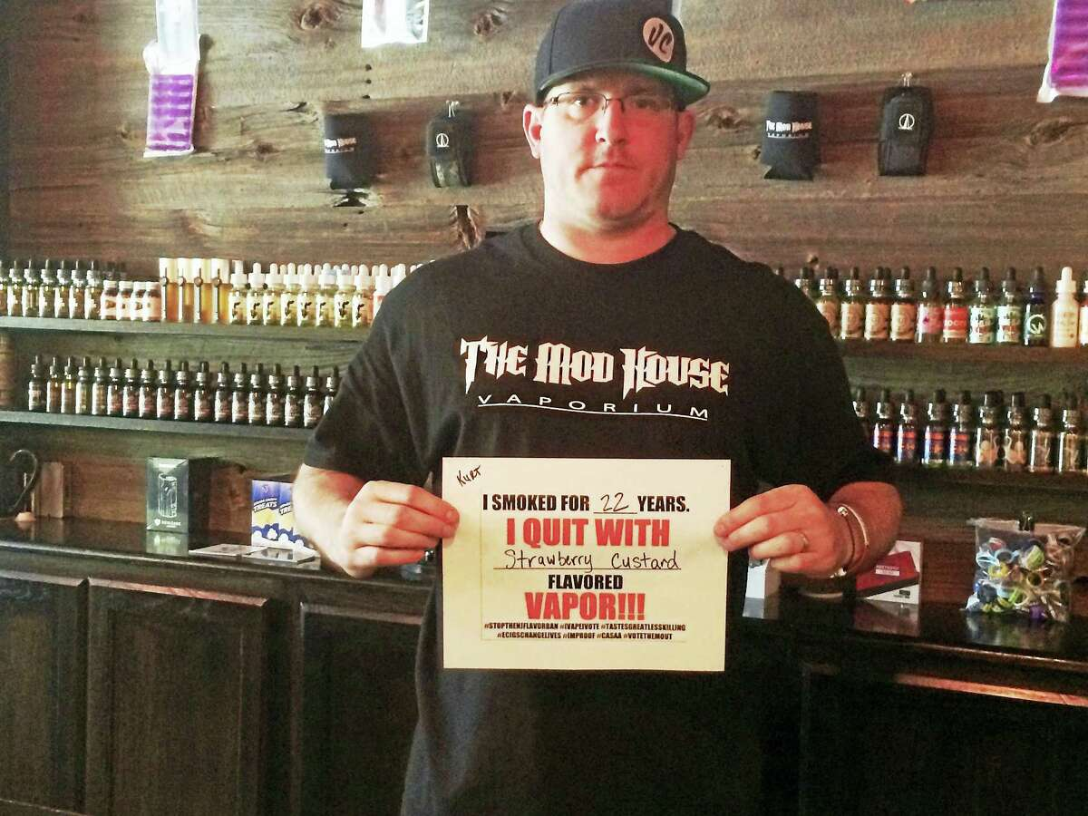 Kurt Buckholz, co-owner of The Mod House Vaporium stores in Milford and Wallingford, stands in the Milford store with a sign that shows what flavor e-cigarette he used to quit smoking tobacco.As state and federal policy-makers debate regulations for the e-cigarette industry, shop owners say it's key they don't ban flavored liquids.