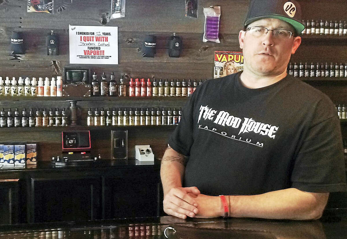 Kurt Buckholz, co-owner of The Mod House Vaporium stores in Milford and Wallingford, stands behind the counter of the Milford store.