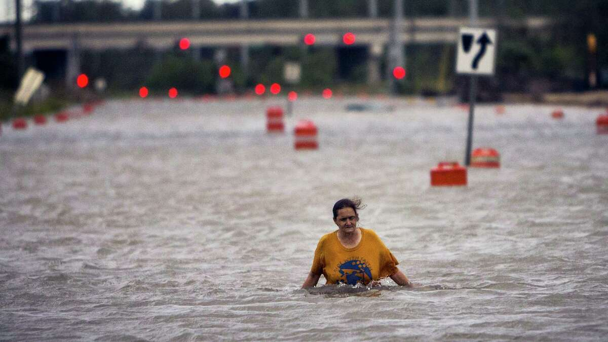 A woman who identified herself as Valerie walks along flooded President Street after leaving her homeless camp after Hurricane Matthew caused flooding, Saturday, Oct. 8, 2016, in Savannah, Ga. Matthew plowed north along the Atlantic coast, flooding towns and gouging out roads in its path.
