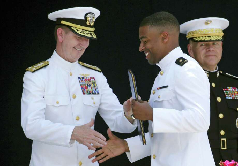 U.S. Naval Academy Superintendent Ted Carter Jr., left, presents a diploma to Keenan Reynolds, graduating Midshipman and the Baltimore Ravens' sixth round NFL draft pick, during the Academy's graduation and commissioning ceremony in Annapolis, Maryland, on May 27. Photo: ASSOCIATED PRESS  / Copyright 2016 The Associated Press. All rights reserved. This material may not be published, broadcast, rewritten or redistribu